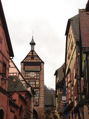 Riquewihr high street, France.  Half timber houses and clock tower.
