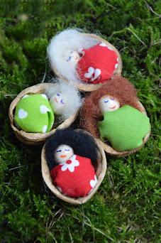 Selbst gemachte kleine Püppchen im Walnussbett