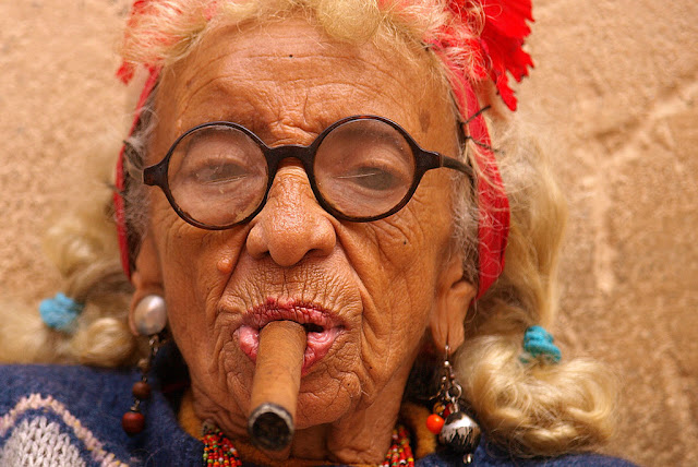 """Cigar smoking woman in Cuba"" by Tibor Végh - Kuba 996.jpg. Licensed under CC BY 3.0 via Wikimedia Commons - https://commons.wikimedia.org/wiki/File:Cigar_smoking_woman_in_Cuba.jpg#/media/File:Cigar_smoking_woman_in_Cuba.jpg"