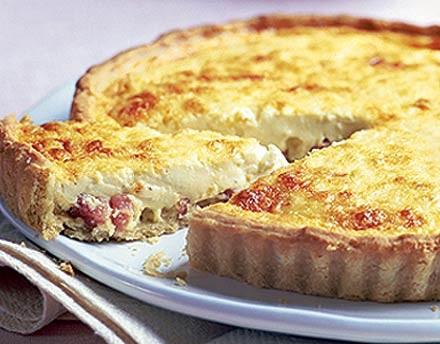 Una vez preparada la pasta (ya sea comprada o hecha por vosotras en casa), rellenamos un molde de tarta. Repartimos por el fondo láminas de queso finas,
