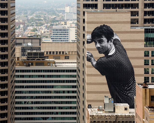 JR recently spent some time in Philadelphia where he was invited by the city's Mural Arts Program to work his craft on the side of a enormous building.