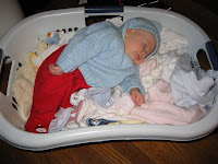 sleeping baby in laundry basket of clean clothes