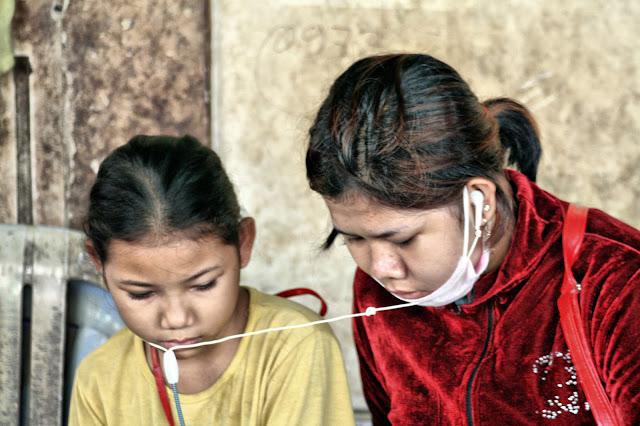 Adolescentes dans un marché de Phnom Penh regardant un film sur leur téléphone portable.