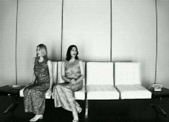 Sonic Youth's Kim Gordon in a beautiful 90's shiny orange dress with Kim Deal of The Pixies and The Breeders in a green dress. Black and White. Still / screenshot from Little Trouble Girl (1995)