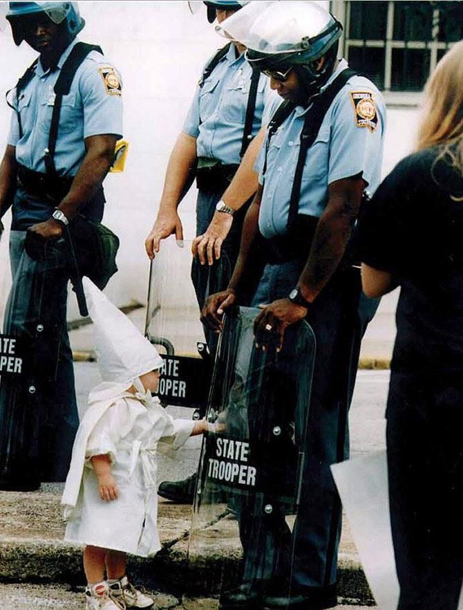 Ребенок дотрагивается до своего отражения в полицейском щите на демонстрации в Джорджии, США, 1992 год.
