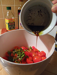Husband's hand pouring dressing into bowl with tomatoes and basil