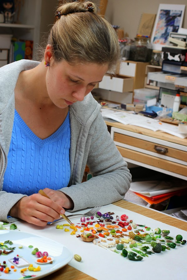 Stephanie Kilgast arranging miniature sculptures together