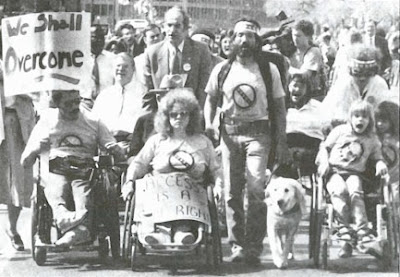 "a black and white picture shows a crowd of people, some of whom use wheelchairs, one man has a service dog with him. They are children and adults and appear to be chanting or singing. One person holds a sign that says, ""We shall overcome."""