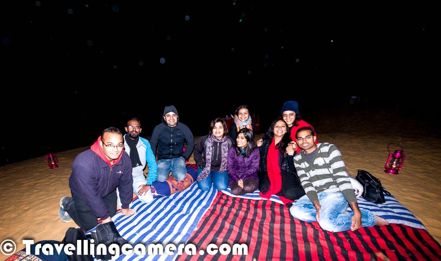 While in Rajasthan and around desert area, it's a must do thing to visit these Deserts & explore a very different type of experience. The Excitement level increases if we plan to have bonfire in the desert under star studded sky. This time 'Malji Ka Kamra' team organized bonfire for us in Desert of Churu. It was one of the most exciting part of our weekend trip to Churu. This Photo Journey shares some of the photographs shot in the desert during Bonfire and some incidents we came across.Many times I planned weekend trips to Rajasthan from Delhi but this was first time when we were in an area surrounded by Deserts. So this weekend trip was quite special for us. During the trip we were staying at 'Malji Ka Kamara' and they arranged this bonfire for us in Desert. The very first experience was driving on Desert and the way SUVs were slipping on sand. We started in 3 cars from Haveli and on the way everyone fit into the SUVs we had. We went ahead on these SUVs as normal cars can't be driven on sand.Whole Gang of Writers and Bloggers was excited to have fun in Desert. All arrangements were already done before we hit the Desert for Bonfire. When we reached, we had to climb up to reach the main place, where lighting & seating arrangements were done. Chef was ready with some Scrumptious snacks. While we were settling there, few folks started setting up the cameras on tripods to shoot stars, star-trails and desert lit with moonlight. Few of us were very focused to keep track of shooting stars.Desert Bonfires in Rajasthan are very popular during the month of December. Many of the tourists hit Rajasthan to celebrate Christmas and New Year in Desert camps. Desert Bonfire on Christmas eve sounds very exciting. And this is what comes to my mind when I think about this - Jingles on Guitar, Cake with Wine and gifts for each other. Bonfire in Desert can bring lot of excitement and craziness. On the same lines, New Year Eve in Desert around bonfire can be very special with friends and family. With time, cost of celebrations of New Year have increased a lot i cities and a Desert Bonfire with friends can be a brilliant option with much lesser cost and a private affair.The sad part of the bonfire was unavailability of drinks in Desert. Malji Team had only beer to offer and many of us couldn't have anything else. I opted for beer and found it very different. I never had such strong beer before. Hope that other guests at Malji Ka Kamara ensure that they arrange drinks themselves or request the team to arrange variety of stuff while in desert. We would have loved to have some options in drinks to enjoy the Desert bonfire better with star studded sky and very frequent shooting stars.Suddenly everyone started noticing the silence of desert and the discussion lead to ghost stories. Now ladies wanted to act like ghosts in the desert. At least they wanted to have some posed photographs in desert by giving some evil impressions. Priyanka lead this shoot and everyone else joined the gang. This was the time, when I got up from my seat and started clicking photographs of these folks. Before that I was feeling lazy and enjoying the beer at Desert Bonfire. Are these stars in above photograph? What do you think?It was time when people wanted there special photographs. It was a real challenge for me because of very low light and didn't want to use flash. So above photograph tells about the process we followed to click various photographs you see in this Photo JourneyBefore visiting Churu, whenever I heard of 'Desert Bonfire', it was mostly about Jaisalmer or Jodhpur in Rajasthan state of India or Saudi. Few of my friends had great time in Jaisalmer, when they stayed in sand dunes and spent most of their time around Deserts only. Hopefully I will plan a trip to Jaisalmer soon.It was an amazing experience of bonfire in Desert. With time, it was getting very cold in the desert and we planned to move back to the Haveli (Malji Ka Kamara) at around 11:30pm. There were lot of things in our To-Do list for next day. We had dinner at the hotel and moved to our rooms to take rest and start the new day with a city tour of Ramgarh.