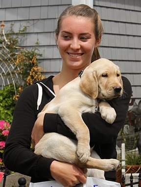 Skyler smiles while holding a young yellow Lab puppy.