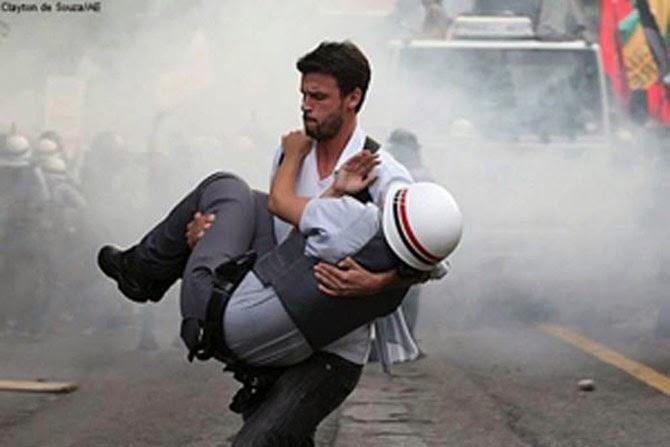 Бразильский демонстрант несет в безопасное место раненого полицейского во время протестов в Сан-Паулу, 2012 год.