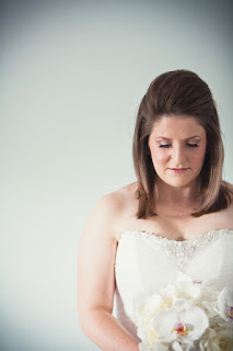 Hair shot of bride against a simple white background, holding a bouquet