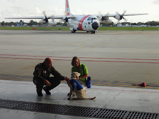 Stephanie and yellow lab Coastie with the large plane with four engines in the background. Coastie is sitting, Stephanie and a member of the Coast Guard is petting Coastie. Photo by Roger Reese.