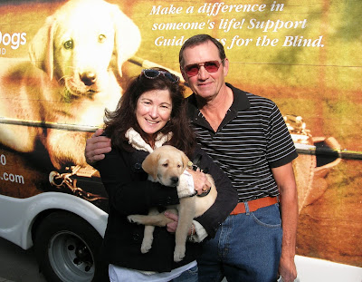 Nancy and Don Bloyer with yellow Lab guide dog puppy January in front of the Puppy Truck