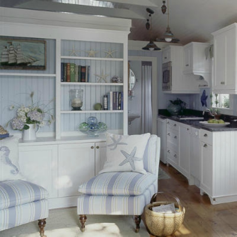 coastal cottage wood planked walls, white kitchen cabinets and blue and white chaises