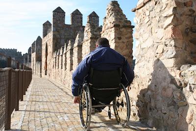 Persona usuaria de silla de ruedas paseando por la parte superior de la Muralla de Ávila