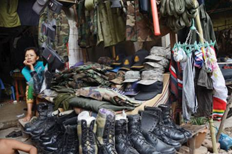 vendor sells military apparel at a clothing stall at Teuk Thla ...