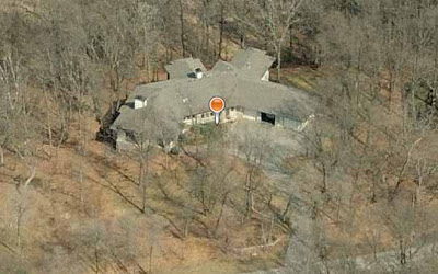 Aerial photo of very large suburban house surrounded by woods