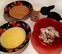 Ingredients for baked Chicken Cordon Blue. Bowls with beaten eggs, chevre filling and ground hazelnut flour