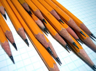 stack of pencils laying on graph paper