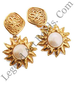 These earrings in the style of Chanel embody the flashiness of the '8os. They are naively patterned, gilded to a high shine, and set with rough faux baroque pearls. They do not stand up to close inspection and are not meant to.