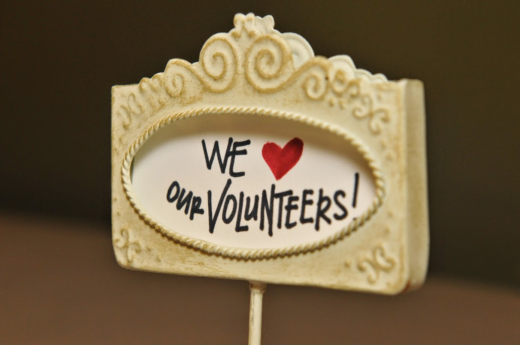 "Table sign that reads ""We LOVE our volunteers!"""