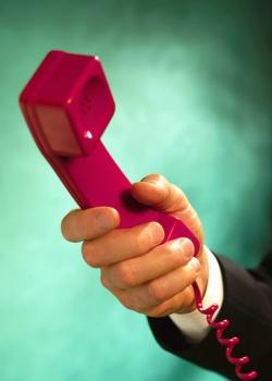 main qui tend un combiné téléphonique