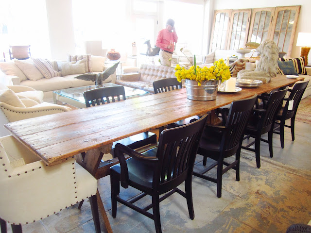 A long farmhouse trestle base dining table with a reclaimed wood top that seats at least 10 is surrounded by black wood chairs and an upholstered host chair with nailhead trim