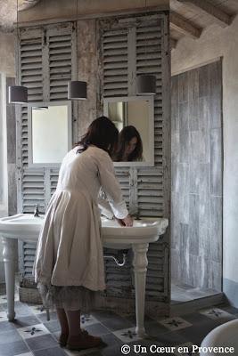 Décoration de salle de bains avec un vieux lavabo double sur pieds posé contre des persiennes chinés, carreaux de ciment et murs badigeonnés