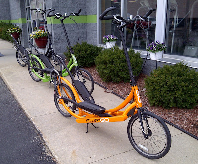 Three ElliptiGO elliptical cycles on a sidewalk