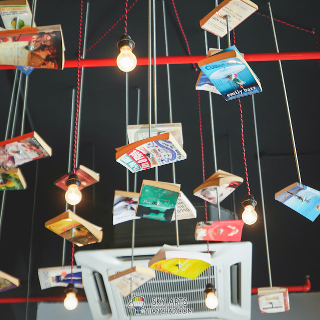 Books hanging in the middle of the air with simple lighting around it