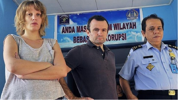 French journalists Valentine Bourrat and Thomas Dandois with an Indonesian immigration official in Jayapura city. Photo AFP via Sydney Morning Herald