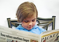 Kid studying a newspaper