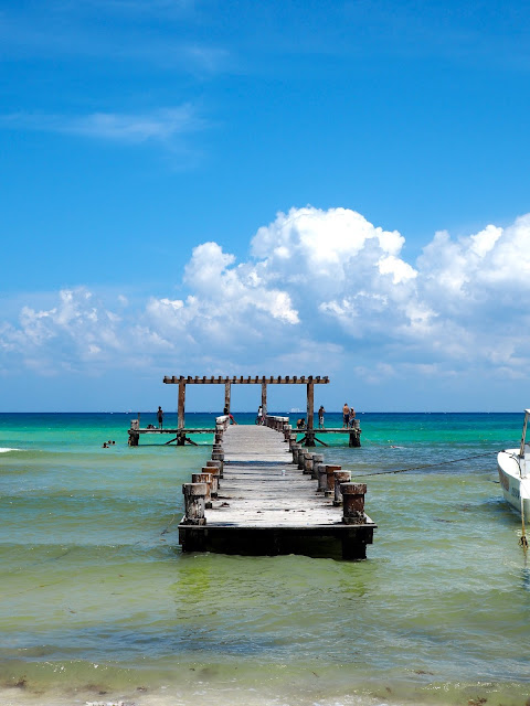 Wooden pier in the turquoise blue ocean at Playa del Carmen beach, Mexico