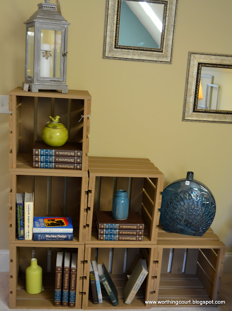 Stacked wooden crates create a bookshelf via Worthing Court blog