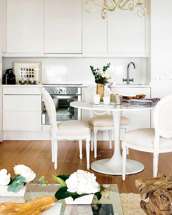 Kitchen in a tiny apartment with wood floor, white Louis XIV chairs, stainless appliances, white cabinets and white countertops