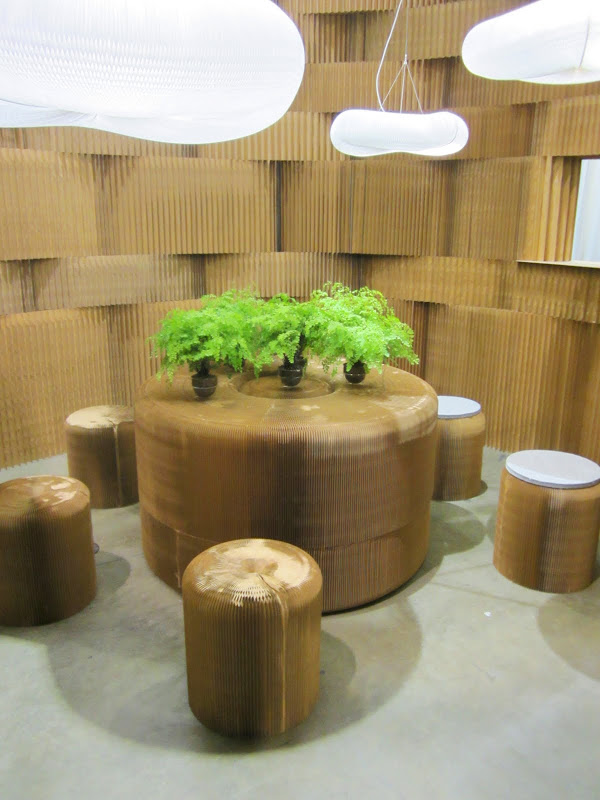 Room with a round table, five stools and a textured wall made out of kraft paper