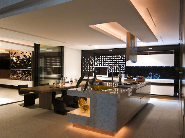 Picture of modern kitchen interiors with marble kitchen island and wooden dining table with black chairs