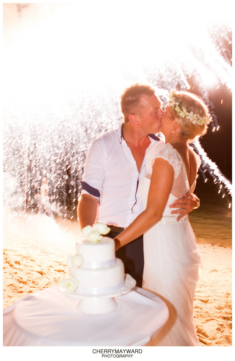 Bride and groom kissing while cake cutting with waterfall of lights backdrop, Koh Samui, Thailand Destination wedding