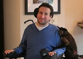 picture of a man in a power wheelchair with a helper monkey onto his shoulder and his arm on his side
