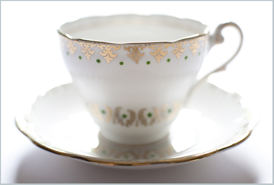 gold and white teacup with green dots