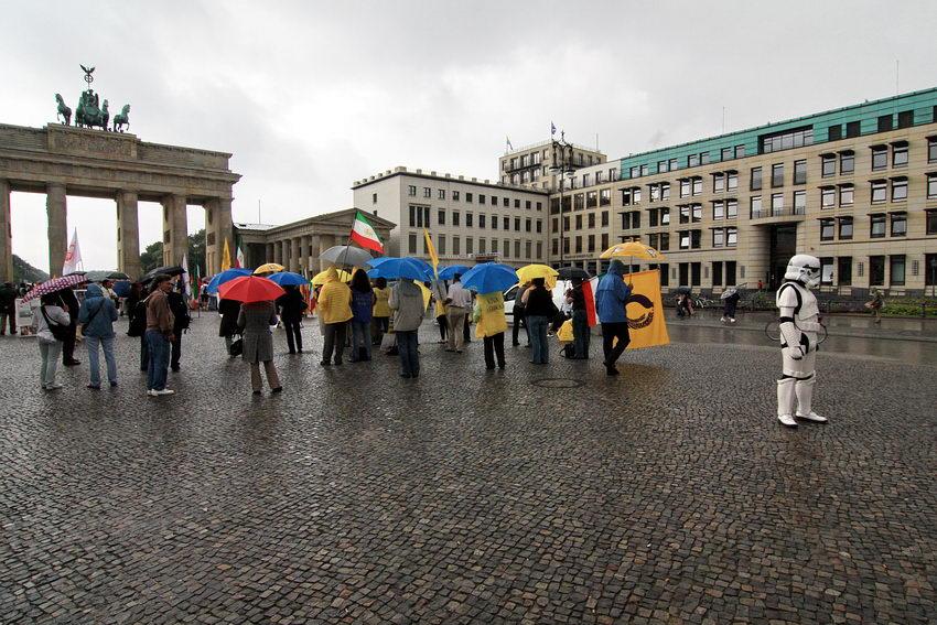 Manifestação junto à Porta de Brandemburgo. Destacado do grupo de pessoas, uma outra vestida com um equipamento semelhante aos habituais no cinema de ficção científica