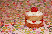 Mini Victoria sponge filled with vanilla buttercream and raspberry jam, topped with a fresh raspberry