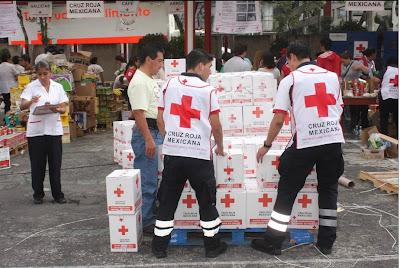 Voluntarios de la Cruz Roja armando ayuda humanitaria.