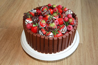 Chocolate and raspberry gateau topped with raspberries and chocolate-dipped strawberries