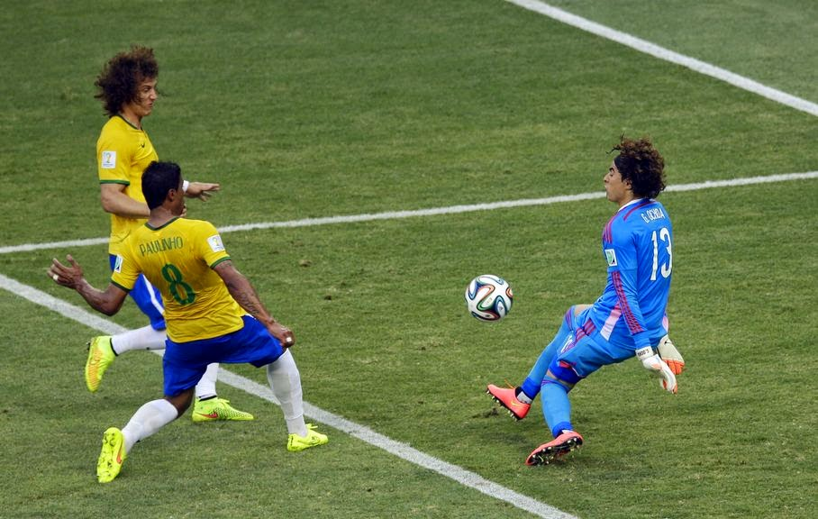 Mexico's goalkeeper Guillermo Ochoa, right, deflects a ball as Brazil's David Luiz, left, and Paulinho approach during the group A World Cup soccer match between Brazil and Mexico at the Arena Castelao in Fortaleza, Brazil, Tuesday, June 17, 2014.