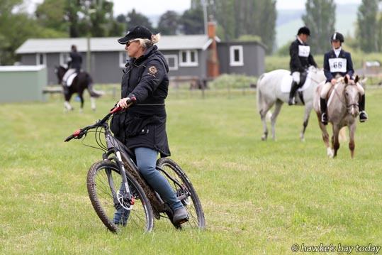 Christine Weal, Te Awamutu, trainer/coach, watching some of her students, gets about on an electric bike - National Eventing Championships, run by Central and Southern Hawke's Bay Eventing, held on Arran Station, Takapau. photograph