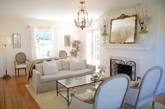 Before and After: Living Room in the Nest; linen sofa and chairs, iron coffee table and fireplace screen, gold chandelier and mirror; Nora's Nest