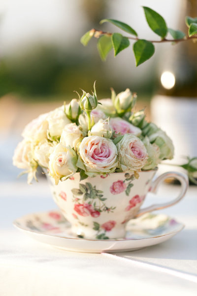 Create delicate table centerpieces with mini roses and teacups