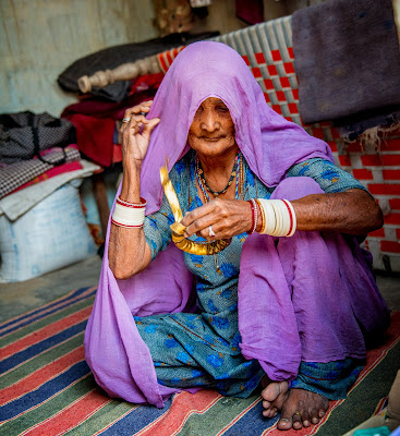 An old lady sitting making and decorating a head ring to sell in Rajasthan, India